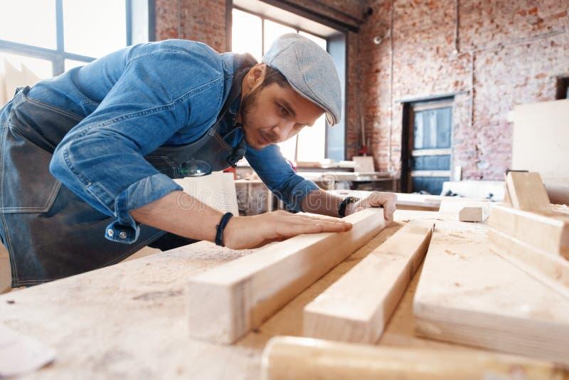 与时髦的盖帽工作的成功的英俊的商人在木匠业方面 库存照片