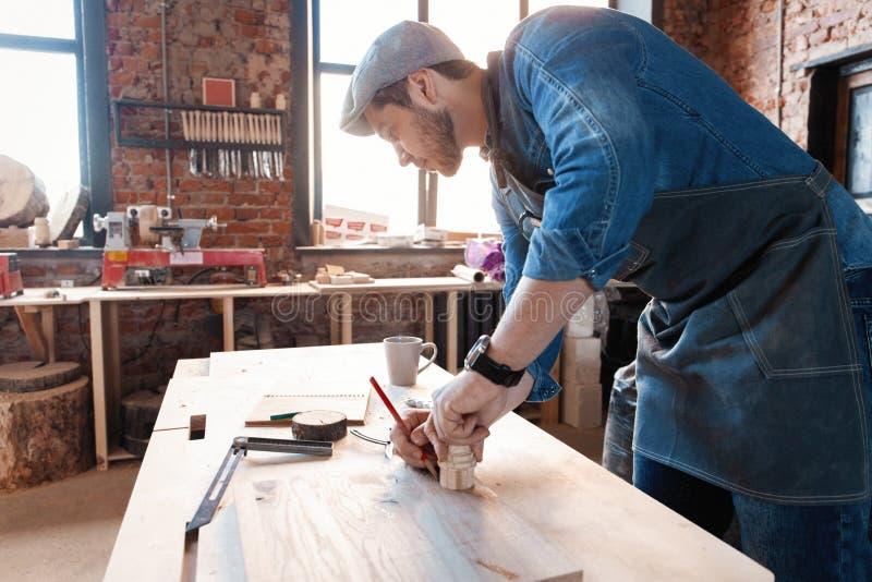 与时髦的盖帽工作的成功的英俊的商人在木匠业方面 图库摄影