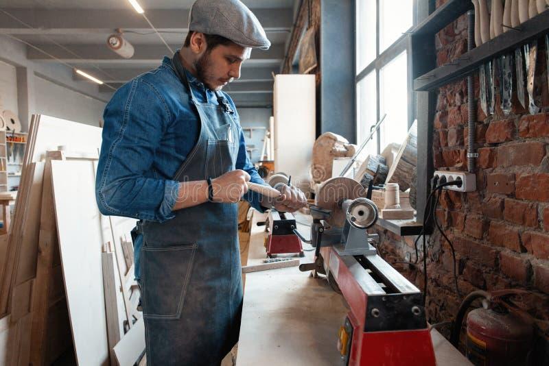 与时髦的盖帽工作的成功的英俊的商人在木匠业方面 库存图片