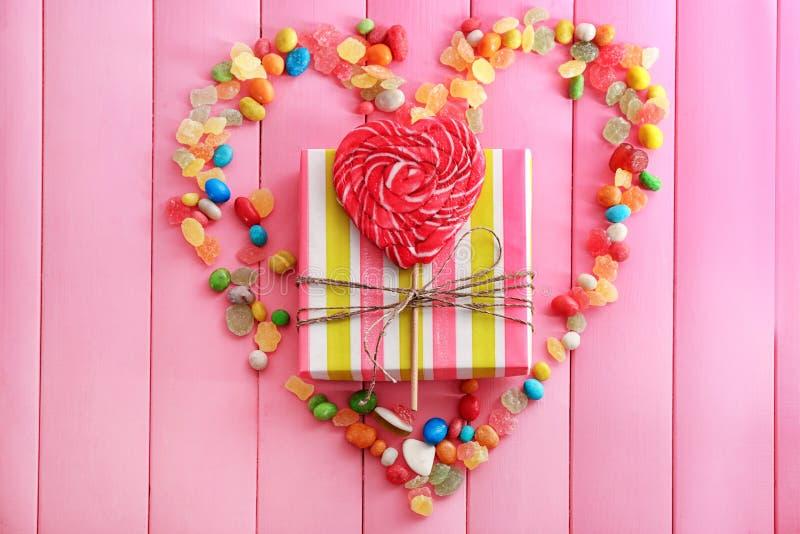与时髦的礼物盒和糖果的构成在颜色木背景 免版税库存图片