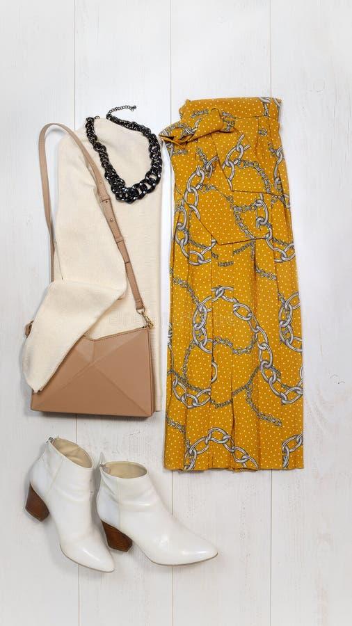 与时髦链印刷品的平的被放置的时尚女性成套装备布局:黄色裙子,毛线衣,首饰,在白色木的袋子起动 免版税图库摄影