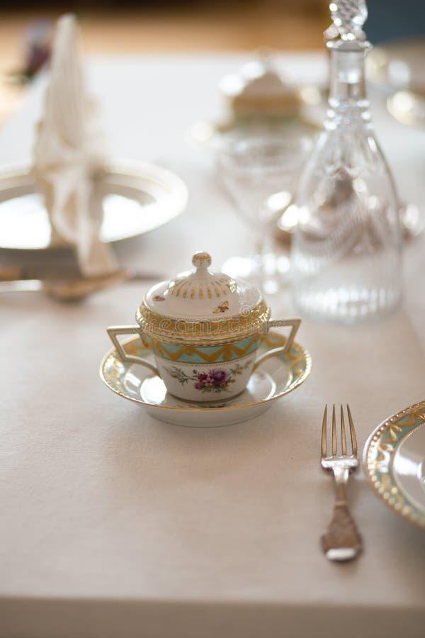 与昂贵的减速火箭的皇家雄伟瓷服务板材和利器的婚姻的桌装饰在宫殿 库存照片