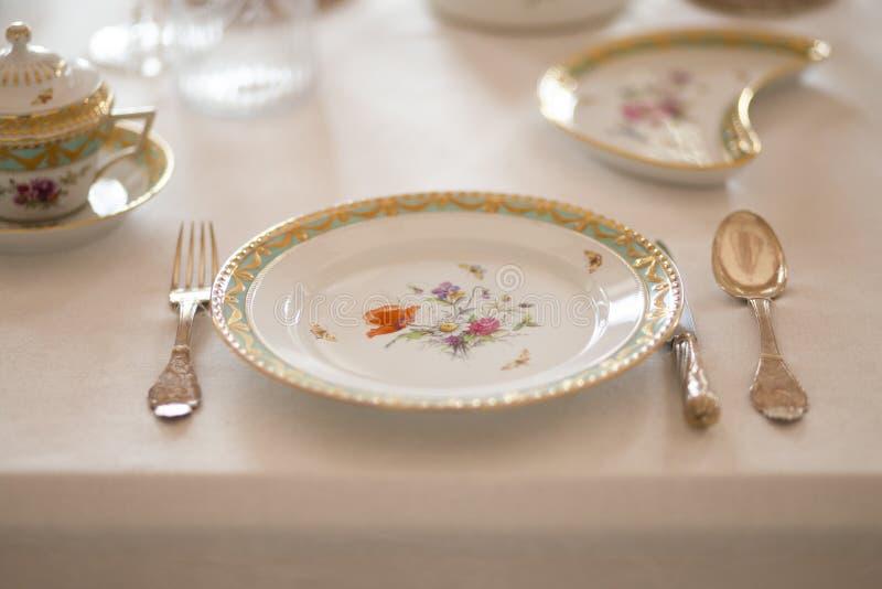 与昂贵的减速火箭的皇家雄伟瓷服务板材和利器的婚姻的桌装饰在宫殿 库存图片