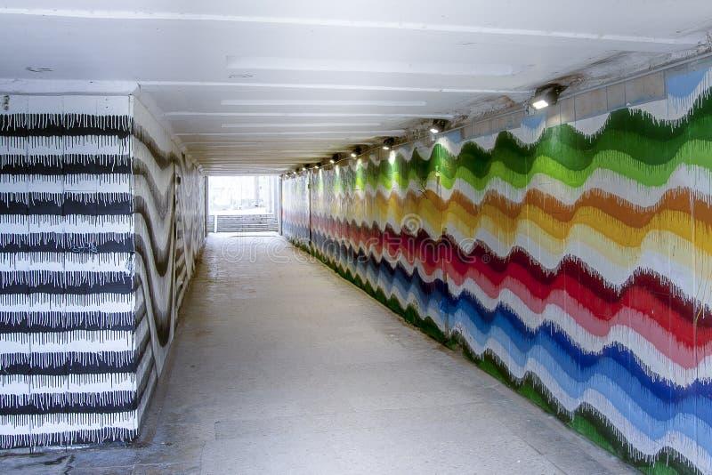 与明亮地被绘的墙壁的地下行人交叉路 库存图片