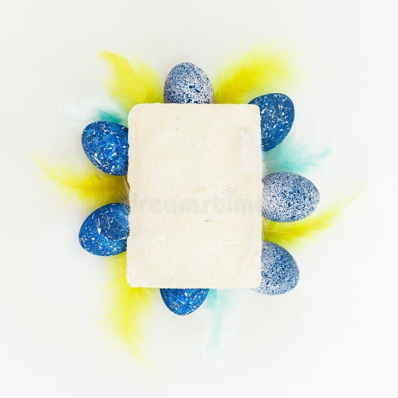 与明亮的五颜六色的羽毛的蓝色复活节彩蛋和在白色背景的纸牌 平的位置 免版税库存照片