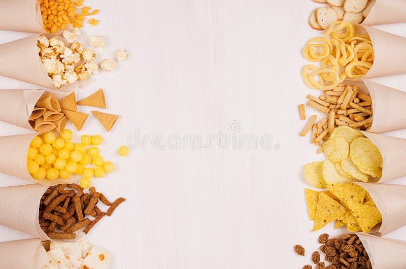 与明亮的嘎吱咬嚼的快餐快餐-烤干酪辣味玉米片,玉米花,油煎方型小面包片,在白色木板,拷贝空间的芯片的米黄纸锥体 库存照片