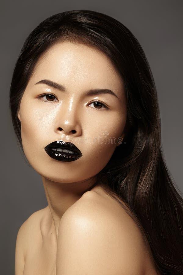 与明亮的嘴唇光泽构成的高档时尚秀丽亚洲模型 有光泽唇膏构成的黑嘴唇 长期黑发 免版税库存照片