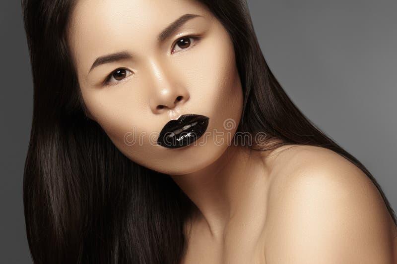 与明亮的嘴唇光泽构成的高档时尚秀丽亚洲模型 有光泽唇膏构成的黑嘴唇 长期黑发 免版税库存图片