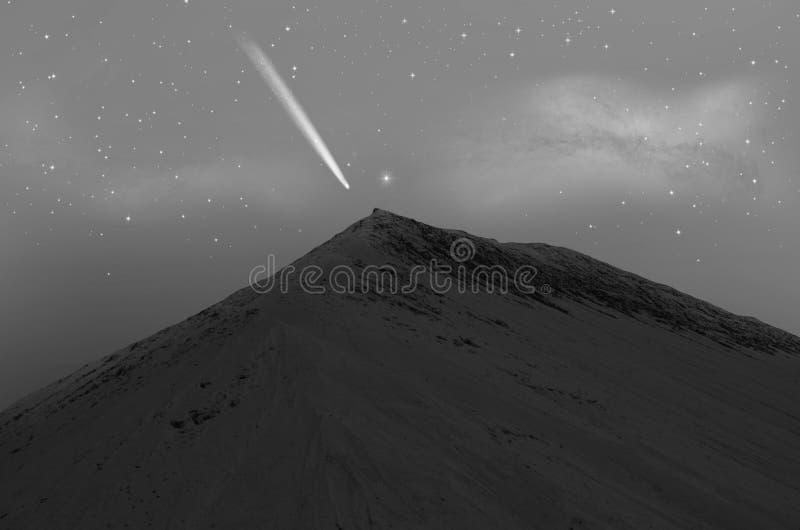 与明亮的彗星的高沙子山在上面 免版税库存图片