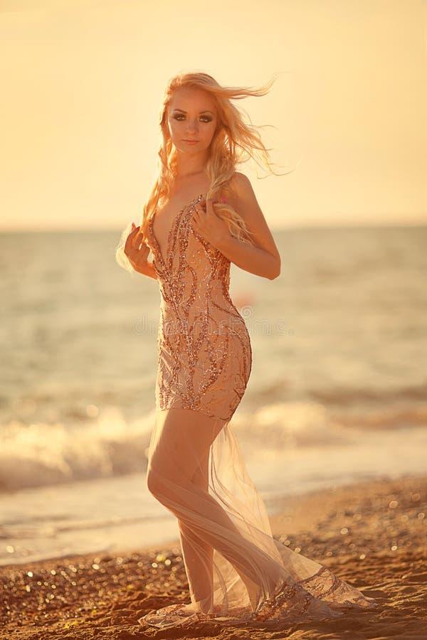 与明亮的户外构成正在流行的样式的白肤金发的少妇模型在蓝天后的晚礼服 免版税库存照片