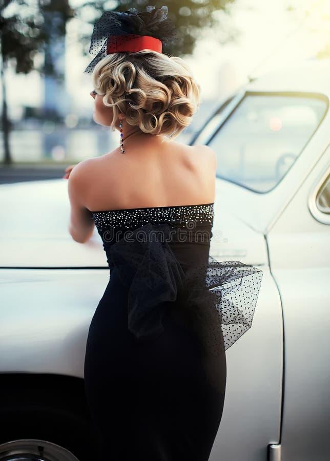 与明亮的构成的白肤金发的女孩模型和在摆在老白色汽车附近的减速火箭的样式的卷曲发型 免版税库存照片