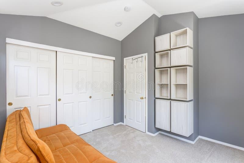 与明亮的橙色沙发的灰色室内部 免版税库存照片