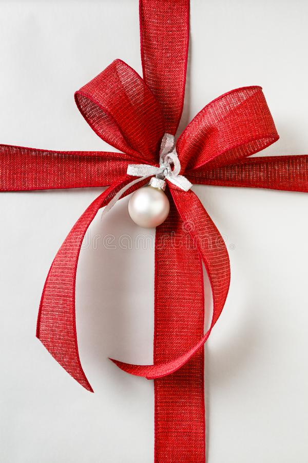 与明亮的红色弓和银色包装纸背景的美好的圣诞礼物礼物 免版税图库摄影