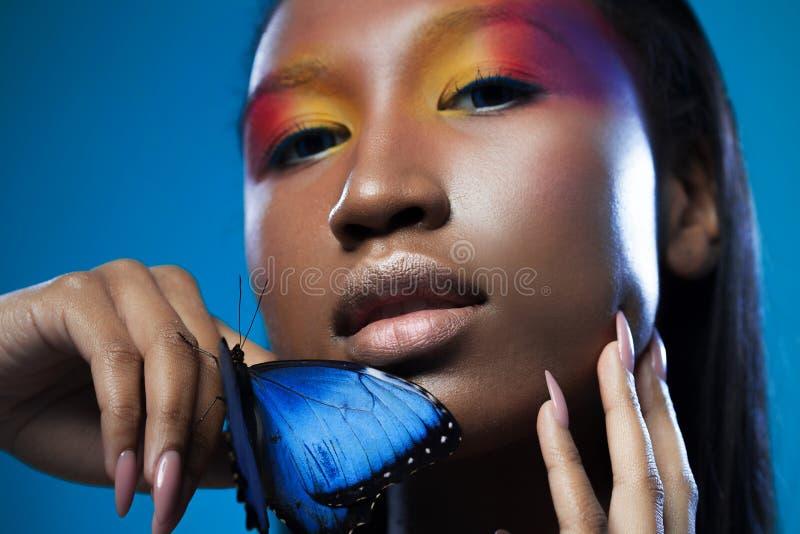 与明亮的蓝色蝴蝶的年轻和美好的黑式样异乎寻常的神色 图库摄影