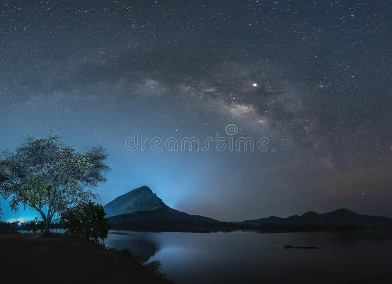 与星和银河的夜空在山和反射上在水 库存图片