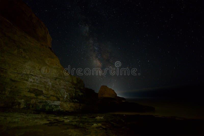 与星和银河的沿海岩石 免版税库存照片