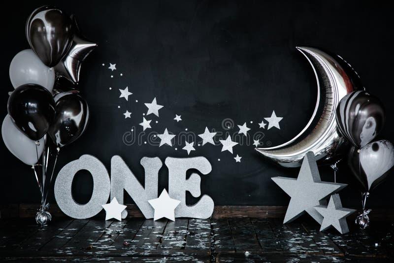 与星的捣毁的第一个生日白蛋糕和小的男婴和装饰的一个蜡烛 黑色背景 大银色lett 免版税库存照片