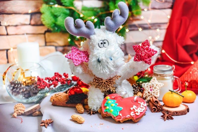 与星的玩具驯鹿在手、tangerins、曲奇饼和明亮的星形状bokeh上 免版税库存照片