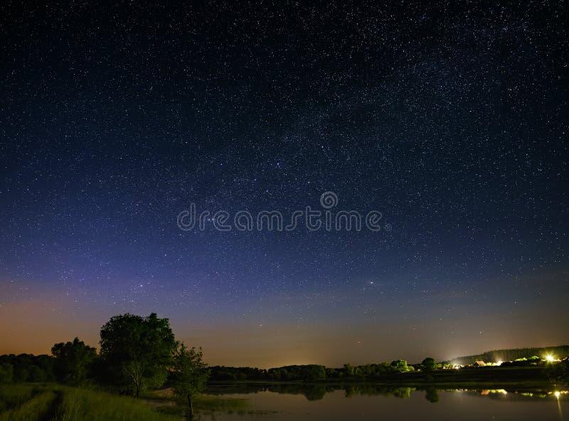 与星的空间在夜空 与河的风景 免版税图库摄影
