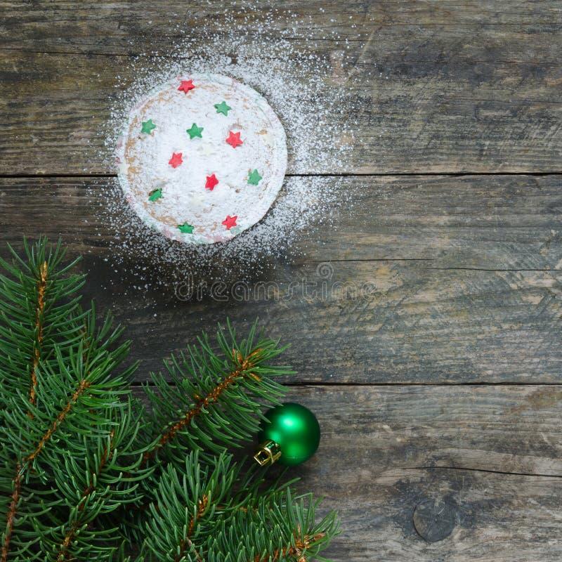 与星装饰的杯形蛋糕 绿色圣诞节球和圣诞树在老木背景 图库摄影