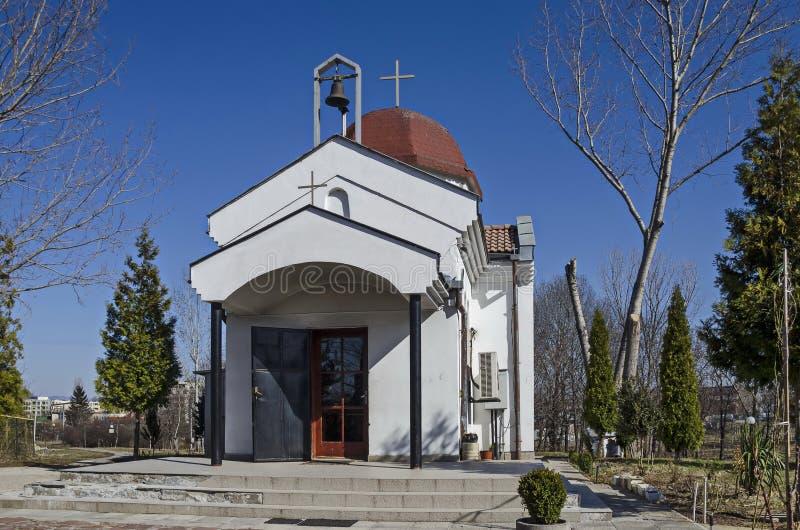 与春天树和小秀丽教会的美好的风景,位于Drujba区 免版税库存照片