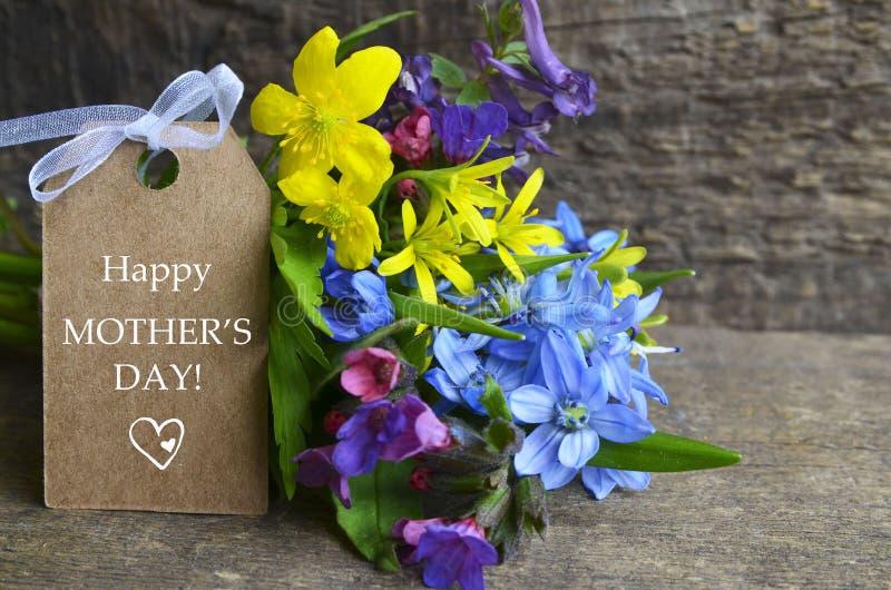 与春天的愉快的母亲` s天贺卡开花在老木背景的花束 库存照片