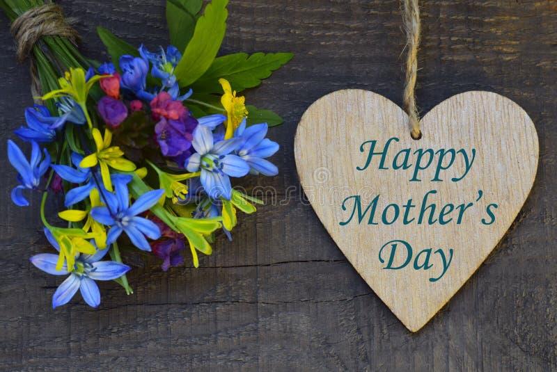 与春天的愉快的母亲` s天贺卡开花花束和装饰心脏在老木背景 免版税库存照片