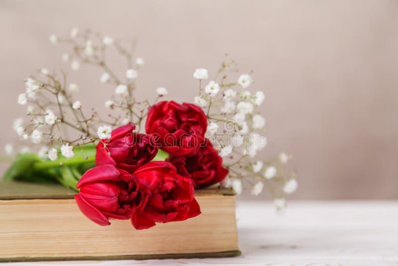 与春天红色郁金香和一本书的葡萄酒静物画在米黄背景 母亲节,妇女的天概念 免版税库存照片