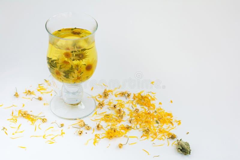与春黄菊、薄菏和金盏草花的草本医药自然茶 免版税库存照片