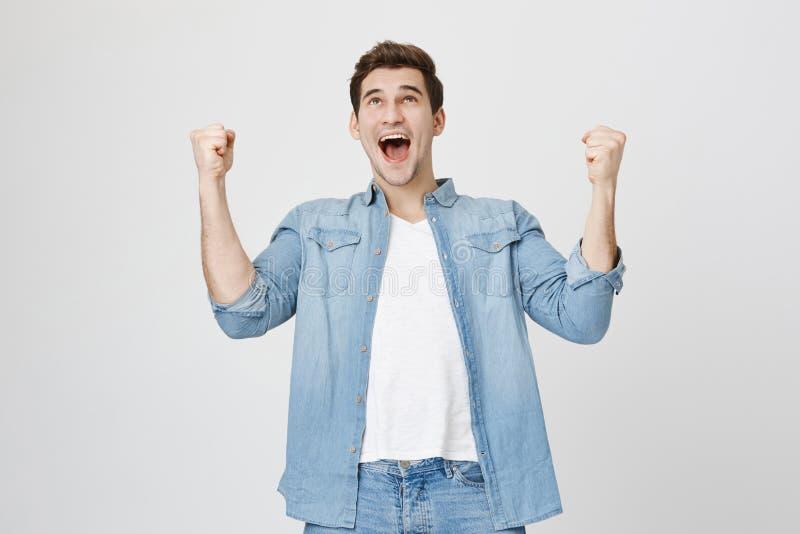 与是张的嘴的快乐的深色头发的可爱的欧洲不剃须的男性激动和高兴获得胜利 免版税图库摄影