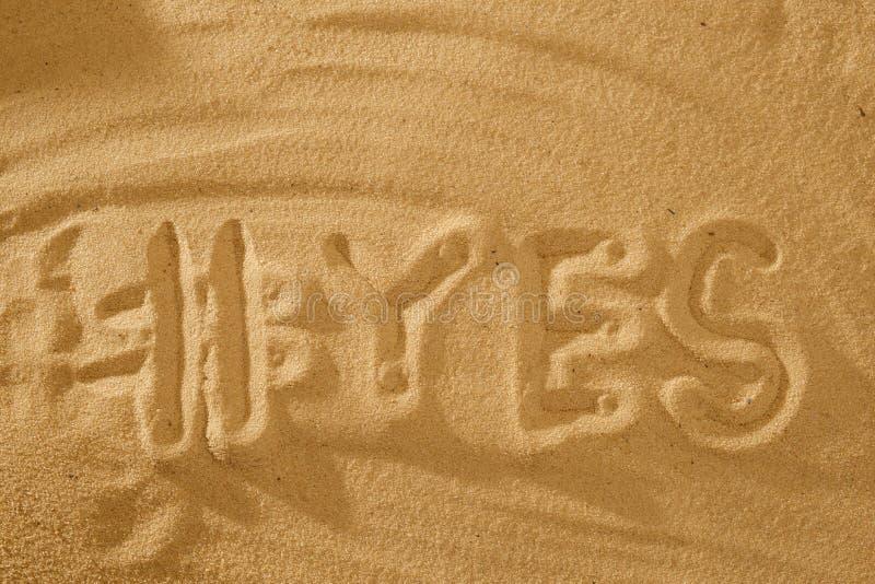 与是hashtag的词在反对海太阳的沙子 假日的概念标志 库存照片