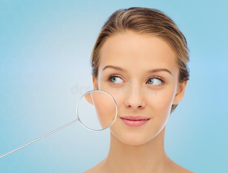 与显示好皮肤的放大器的少妇面孔 免版税图库摄影
