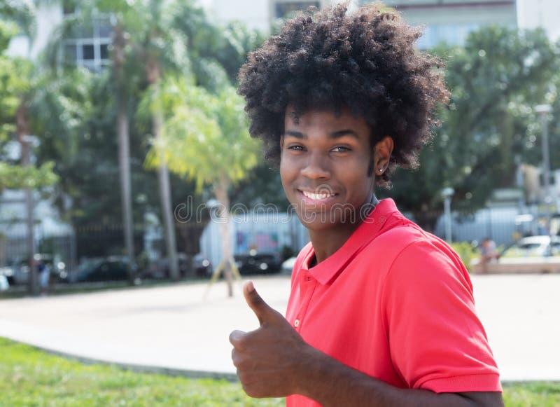 与显示拇指的典型的非洲的发型的非洲年轻成人 库存照片