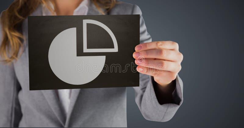 与显示白色圆形统计图表的黑卡片的女商人中间部分反对灰色背景 免版税图库摄影