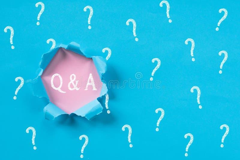 与显露Q&A词的问号的蓝色被撕毁的纸 免版税库存照片