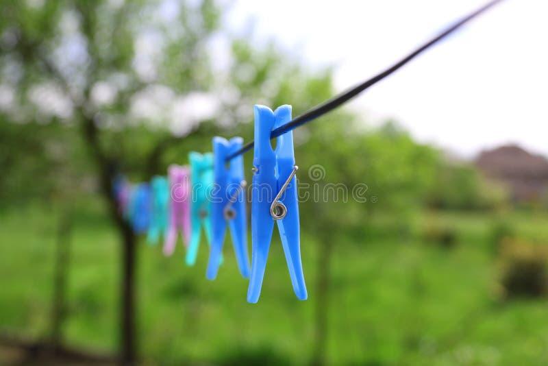 与晒衣夹的绳索在绿色风景背景 免版税库存图片