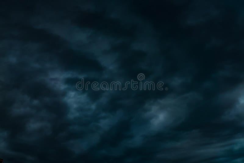 与晚上蓬松卷曲滚动的高积云高层云的深蓝天空背景 免版税库存照片