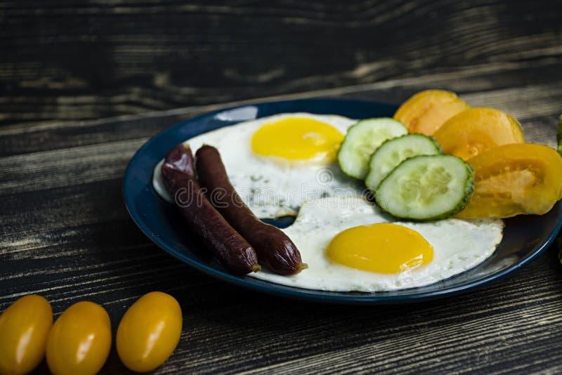 与晴朗的边的自创可口早餐荷包蛋,香肠,在顶视图的蕃茄 免版税库存图片