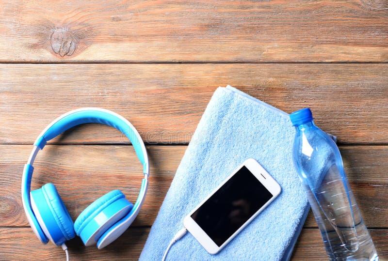 与智能手机、瓶水,毛巾和耳机的平的被放置的构成在木背景 健身房锻炼 库存图片