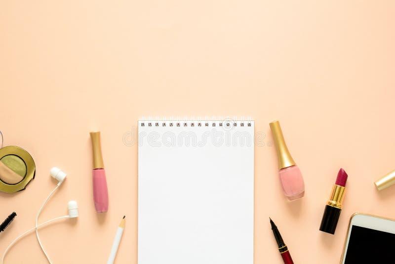 与智能手机、耳机、笔记本、铅笔、指甲油、眼影、染睫毛油和唇膏的女性工作区 平的位置 免版税图库摄影