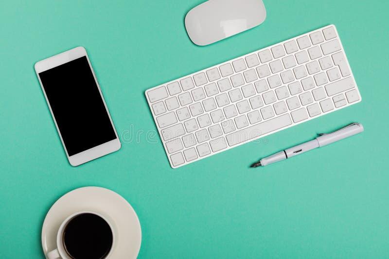 与智能手机、键盘、咖啡和老鼠的办公桌工作区顶视图在与拷贝空间,图表设计师的蓝色背景 免版税图库摄影