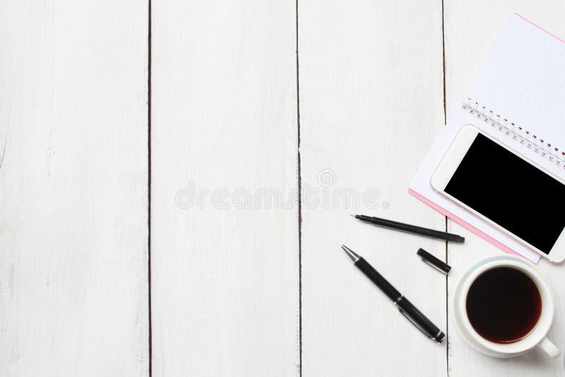 与智能手机供应和co的顶视图白色木书桌桌 免版税库存照片