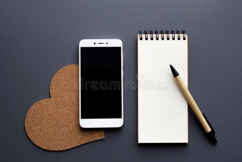 与智能手机和笔的空白的笔记薄 库存照片