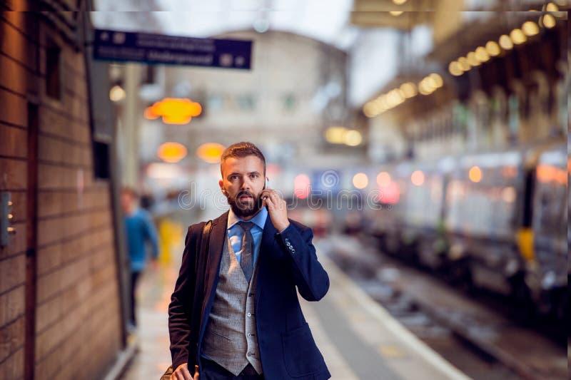 与智能手机的商人,打电话,火车平台 免版税图库摄影