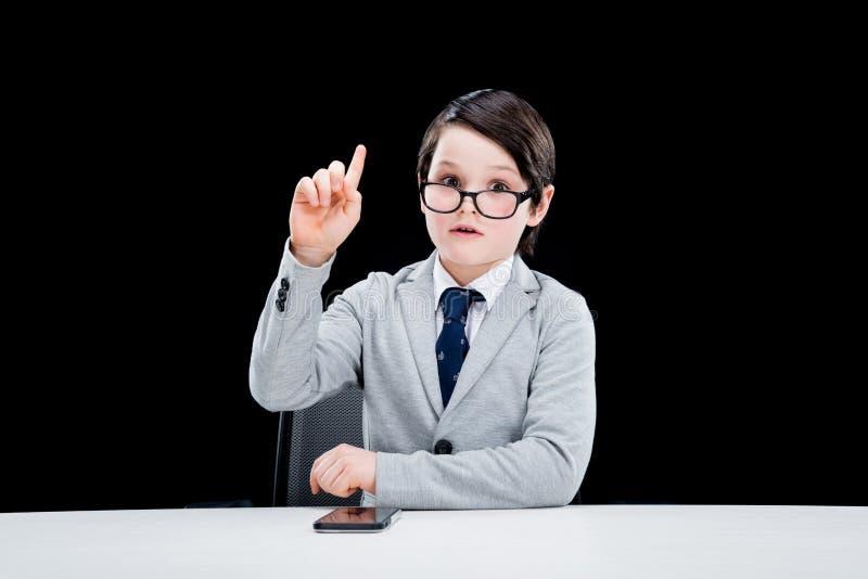 与智能手机的小男孩商人指向与手指的 图库摄影
