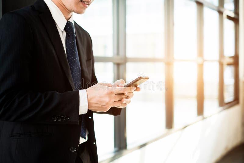 与智能手机的年轻商人身分在办公室窗口附近,企业概念 免版税库存图片