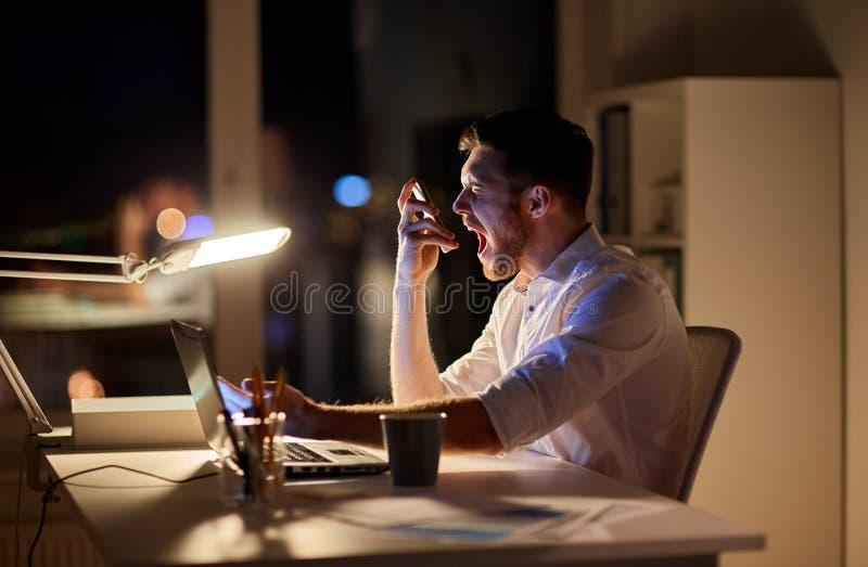 与智能手机的恼怒的商人在夜办公室 库存照片
