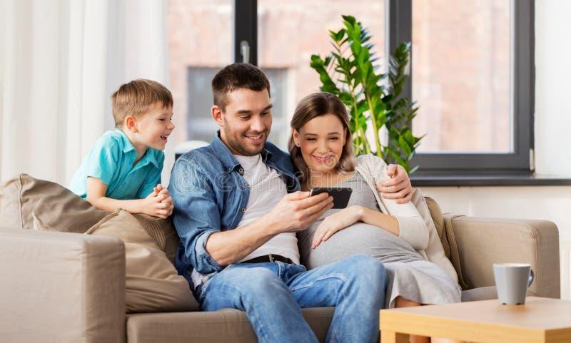 与智能手机的愉快的家庭在家 免版税库存图片
