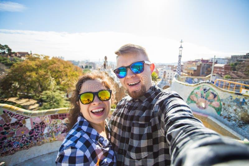 与智能手机的旅行夫妇愉快的制造的selfie画象在公园Guell,巴塞罗那,西班牙 美丽的夫妇年轻人 免版税库存图片