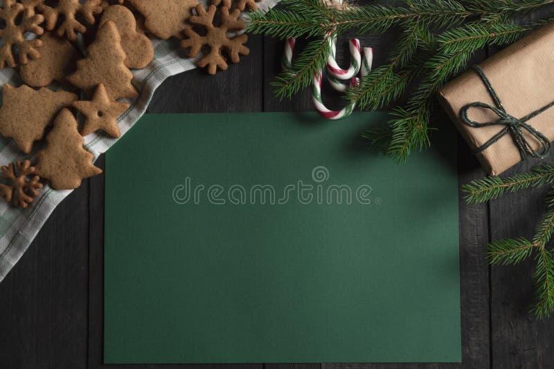 与曲奇饼棒棒糖和礼物的圣诞节框架 空白便条纸 顶视图 复制空间 免版税库存图片
